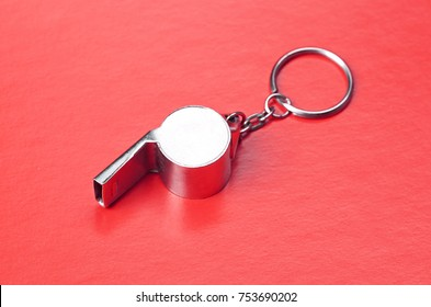 Sports or coaches metal whistle, closeup. Concept refereeing sport on red card background. Soccer or football referee whistle and caution cards