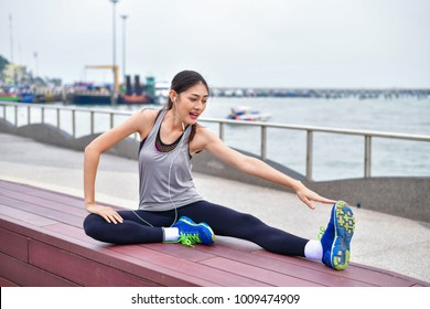 Sports concept. Beautiful girl is exercising on the beach with warm up. Beautiful girl is happy to exercise. 