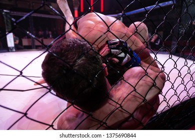 Sports concept of fighting without rules.Two boxer athletes in the arena of the octagonal scene. An alternative look at boxing fights through the metal cage. Submission wrestling