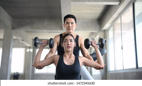 Sports concept. The girl is training dumbbells with the trainer in the fitness.