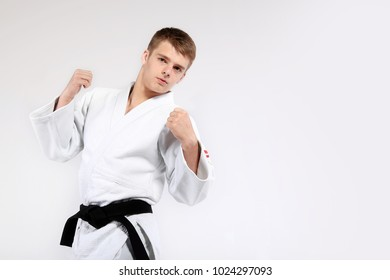 Sports concept. Judo, karate, black belt. A young man in a white kimono for sambo, judo. Portrait of a man karate in a white kimono in a fighting position, close-up. Black and light background