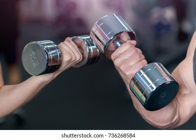 Sports concept. Male and female hand with dumbbells.