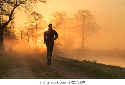Sports concept: silhouette of a man running during a foggy, spring sunrise in the countryside.