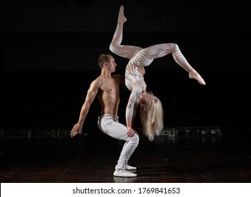 A sports couple of acrobats performs the trick. Acrobats on a dark background.