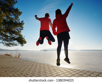 Sports couple crazy jumping on park path around frozen lake. City sport park with pavement on shore. Woman with man excercise  together.