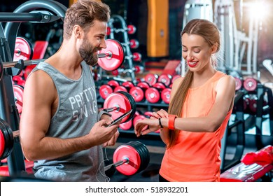 Sports couple standing with smart phones resting after the training in the gym with red dumbbells on the background