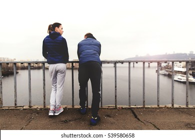 Sports couple talking at the bridge on the morning, back view, copy space
