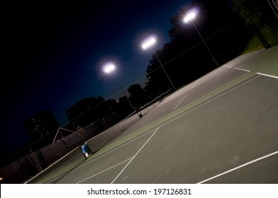 A sports court with an urban scene in the background at night.