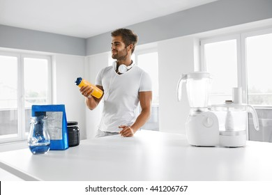 Sports Energy Drink. Handsome Healthy Happy Man With Fit Muscular Body In Sportswear, Headphones With BCAA Amino Acid Beverage And Bodybuilding Nutrition Supplements In Kitchen Before Fitness Workout