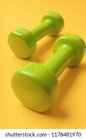 Sports equipment in close up. Barbells in small size made of plastic. Shaping and sport regime concept. Dumbbells in bright green color isolated on yellow background.