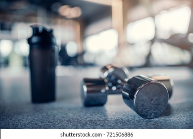 Sports equipment in gym. Shaker and dumbbells on the floor.
