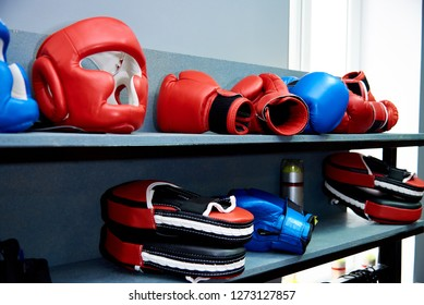 Sports equipment for hand-to-hand combat.A protective helmet, gloves and Boxing paws lie on a shelf.