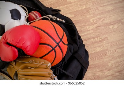 sports equipment in a holdall sports bag on a gym floor. football, baseball, cricket, basketball, boxing. with copy space.