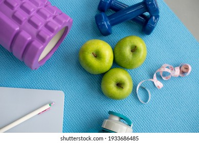 Sports equipment is laid out on the mat: a roller, dumbbells, a diary and a pen, green apples, a tape measure and a bottle of water. View from above.