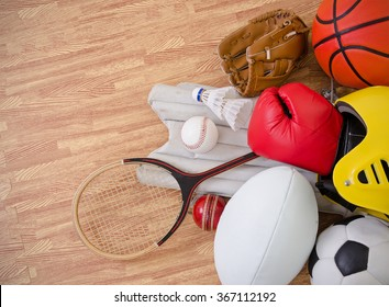 sports equipment on a gym floor, football, rugby, baseball, cricket, basketball, boxing, badminton, squash and helmet. landscape with copy space.