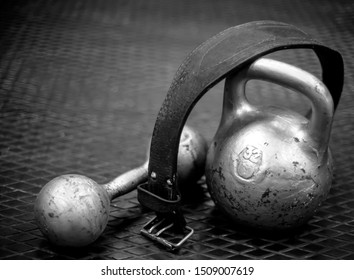 Sports equipment. Still life with weightlifting belt, weights and dumbbells on black background with copy space