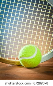 sports equipment.  Tennis and racquet on wood.
