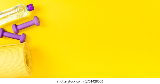 Sports equipment yoga mat, two purple dumbbells for exercises and a bottle of fresh mineral water on a yellow background. Fitness and sport flat lay concept with copy space, banner.