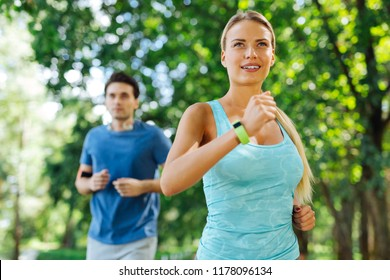 Sports exercise. Delighted nice woman being in the park while jogging in the morning