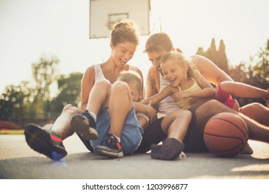 The sports family is a healthy family. Family on basketball playground.