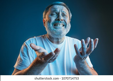 Sports, fan human emotions and people concept - sad senior man watching sports on tv and supporting team at home. Crying emotional man screaming in colorful bright lights at studio. Facial expression