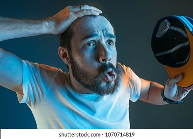 Sports, fan human emotions and people concept - sad young man watching sports on tv and supporting team at home. Crying emotional man screaming in colorful bright lights at studio. Facial expression