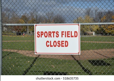 Sports field closed sign hanging on the wire fence
