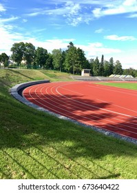 Sports field on a sunny summer day. Running tracks and green football field.