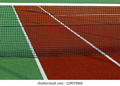 Sports field with synthetic turf, markings and netting used in tennis.Detail.