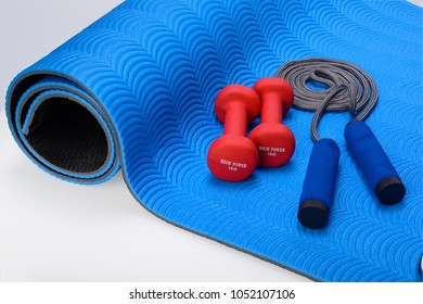 Sports fitness accessories on blue training mat. Frame, healthy.