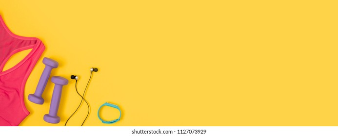 Sports and fitness accessories on yellow background. Flat lay, top view, banner for website.