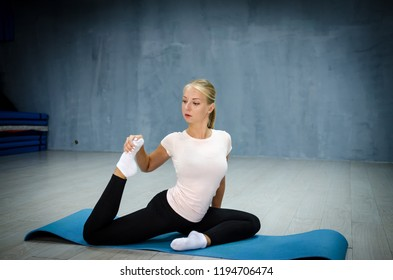 Sports. Fitness woman stretching legs in gym