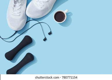 Sports flat lay with coffee, dumbbells, sneakers and earphones on blue background