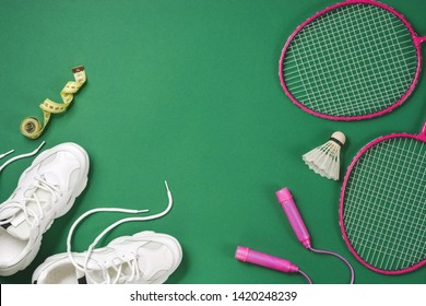 Sports flat lay with shuttlecock and badminton racket, skipping rope, sneakers and measuring tape on green background. Fitness, sport and healthy lifestyle concept.