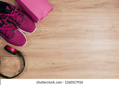 Sports flat lay with sneakers yoga mat and headphones on wooden floor background,Top view concept.