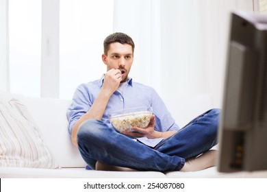 sports, food, happiness and people concept - man watching tv and eating popcorn at home