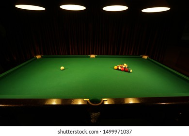 Sports game of billiards on a pool table with green cloth. Multi-colored billiard balls on the playing field. Leisure. Pool table and billiard balls close up. Game billiards, lamps, interior