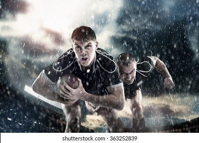 Sports, game, fighting - Rugby players on a stadium in the rain