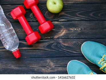 Sports games, dumbbells, drinking water, green apple on a wooden table