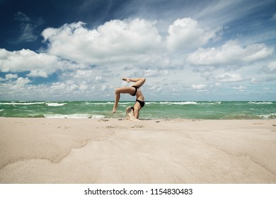 sports girl in a bathing suit is engaged in the gymnastics on the seashore