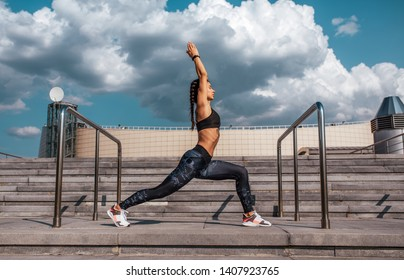 Sports girl doing lunges in the summer in city, practicing yoga. Sportswear leggings top sneakers, woman in harmony. Background clouds steps building.