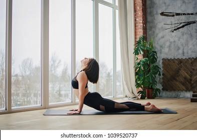 Sports girl doing yoga at home near window