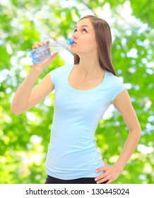 Sports girl drinking water on the street.