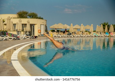 Sports girl jumping into the pool with splaches and reflection in water