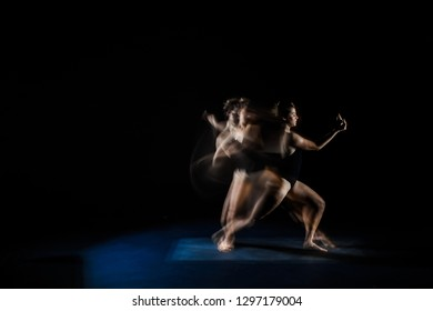 Sports girl performs dancing and fighting movements on a dark background. Portrait of a gymnast and dancer. Drawing by light. Frieze light.
