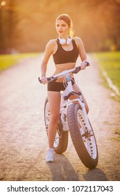 sports girl in a shirt and shorts stands near a steep bike at sunset in the park