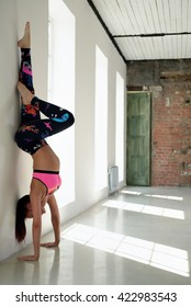 Sports girl stand on hands at wall in yoga position