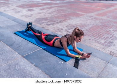 sports girl summer city, lies on yoga mat, listens watches online training, video podcast, writes message on phone, online app on Internet, leisure fitness jogging workouts morning. Leggings.