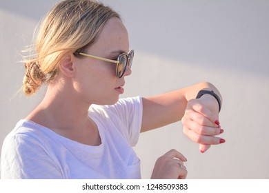 sports girl is switching on her fitbit bracelet tracker before training
