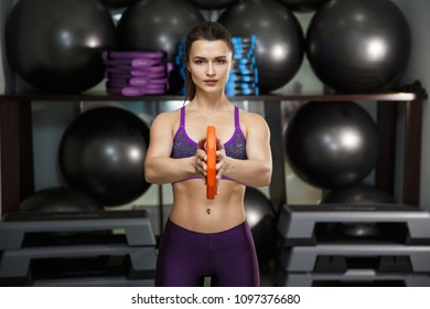Sports girl trains and exercises in the gym.